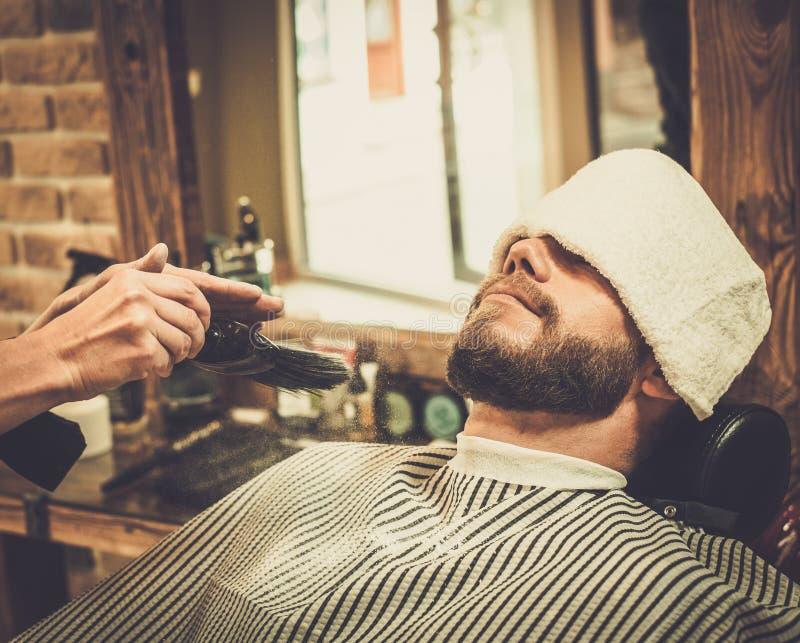 Herrenfriseur, der Bartpulver anwendet lizenzfreie stockbilder