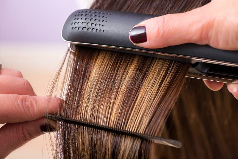 Herrenfriseur, der das Haar eines Kunden geraderichtet stockfotos