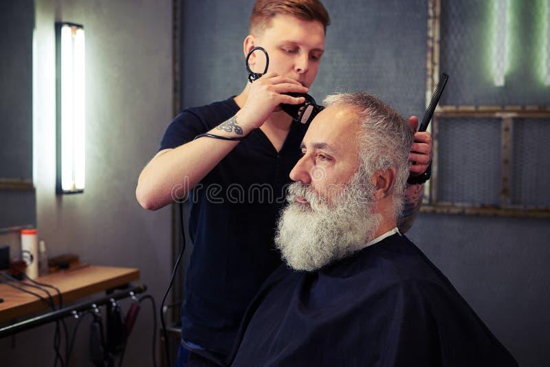 Herrenfriseur, der einem attraktiven bärtigen Mann den Haarschnitt der Männer macht lizenzfreies stockbild