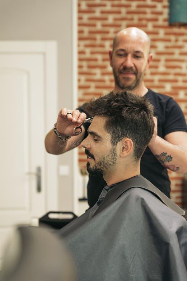 Herrenfriseur, der einem attraktiven Mann den Haarschnitt der Männer macht lizenzfreie stockbilder