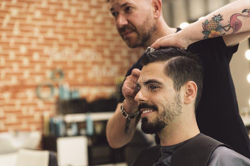 Herrenfriseur, der einem attraktiven Mann den Haarschnitt der Männer macht stockfotos