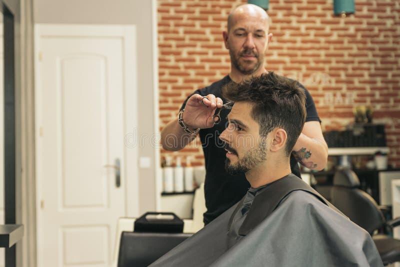 Herrenfriseur, der einem attraktiven Mann den Haarschnitt der Männer macht stockfotografie