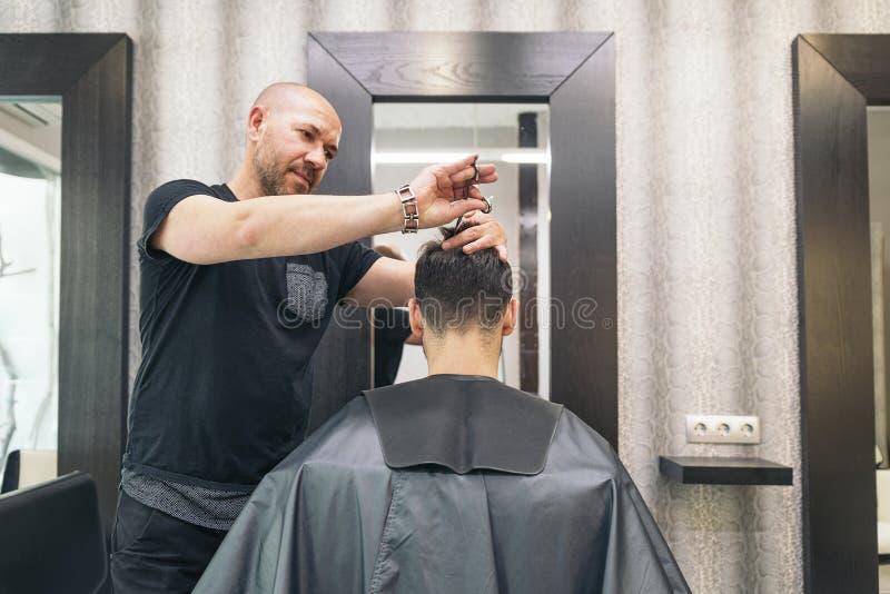 Herrenfriseur, der einem attraktiven Mann den Haarschnitt der Männer macht stockbilder