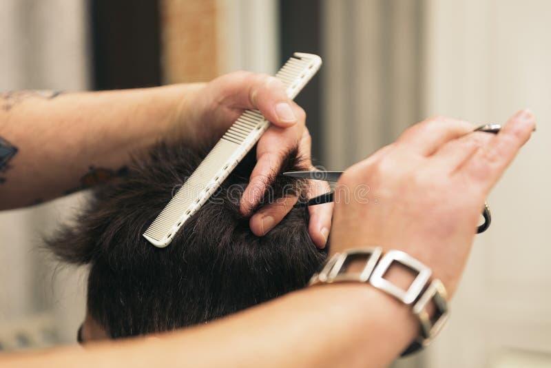 Herrenfriseur, der einem attraktiven Mann den Haarschnitt der Männer macht stockbild