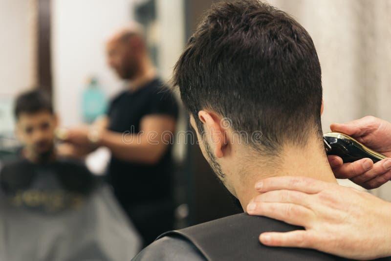 Herrenfriseur, der einem attraktiven Mann den Haarschnitt der Männer macht lizenzfreies stockfoto