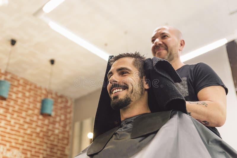 Herrenfriseur, der einem attraktiven Mann den Haarschnitt der Männer macht lizenzfreie stockfotografie