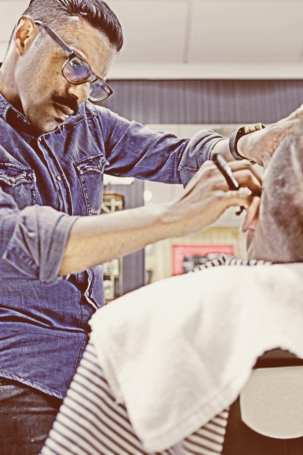 Herrenfriseur, der einen Bart mit einem Rasiermesser rasiert lizenzfreie stockfotos