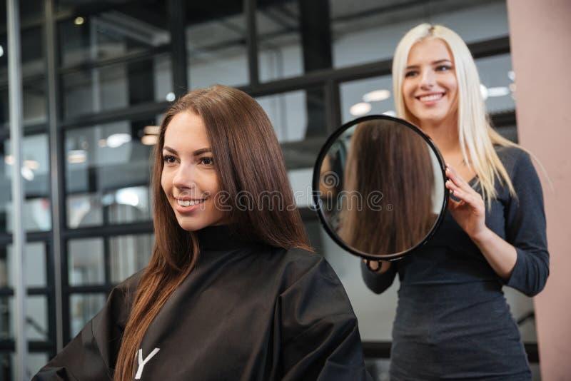 Herrenfriseur, der einer attraktiven Frau den Haarschnitt der Frauen macht lizenzfreies stockbild