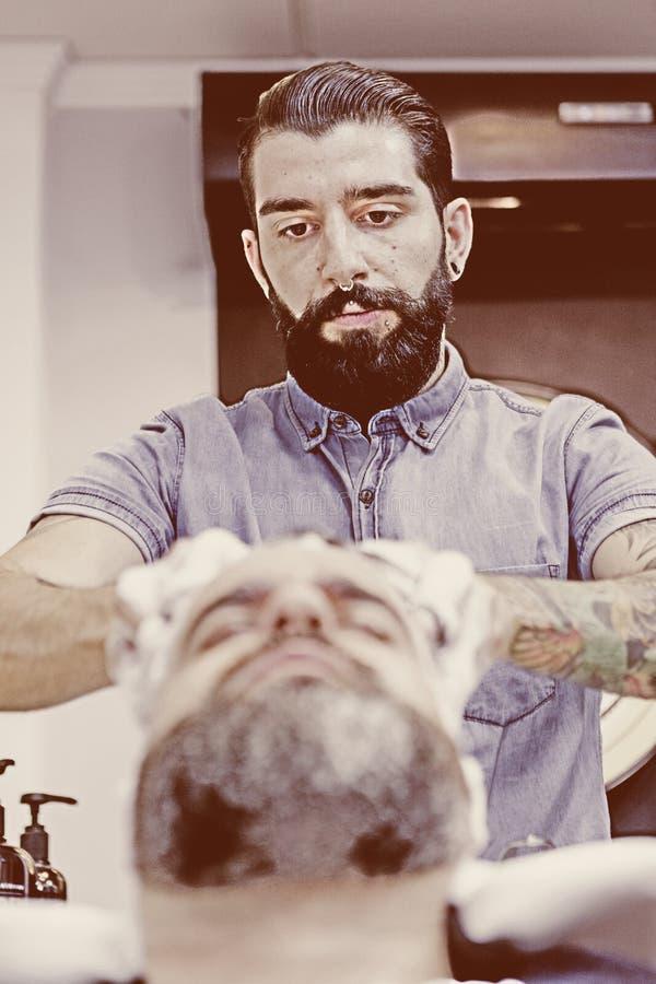 Herrenfriseur, der Haar massiert lizenzfreie stockbilder