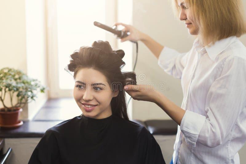 Herrenfriseur machen Locken auf braunem Kunde ` s Haar lizenzfreie stockfotografie