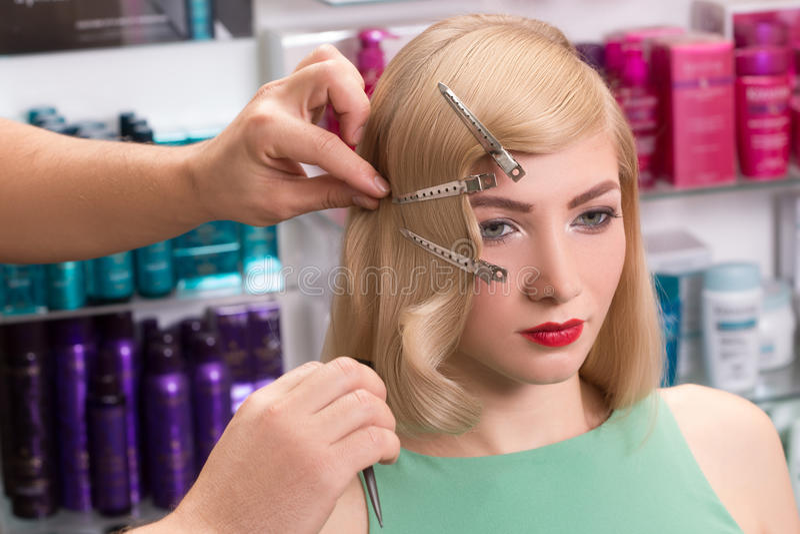 Herrenfriseur macht Frisur für schönes Mädchen stockbilder