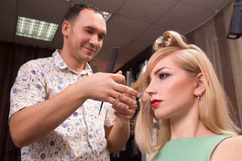 Herrenfriseur macht Frisur für schönes Mädchen lizenzfreie stockfotos