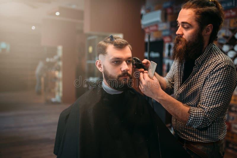 Herrenfriseur macht Frisur vom Kunden im Salonkap lizenzfreie stockbilder