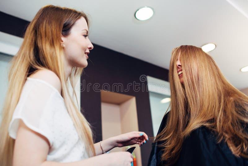 Herrenfriseur und weiblicher Kunde, die mit ihrem Gesicht bedeckt durch das Haar spricht und lacht im Schönheitssalon sitzt stockfotos