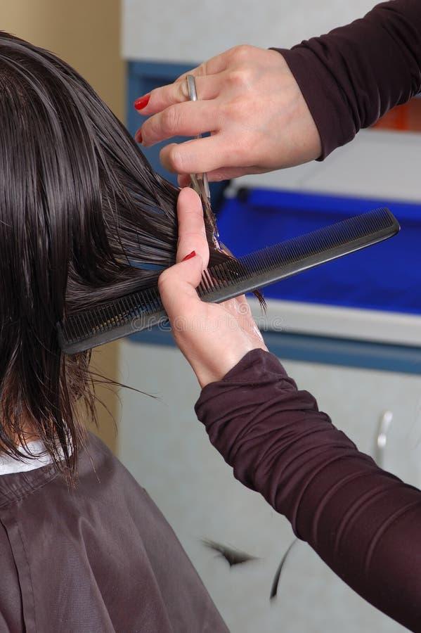 Herrenfriseurhände, die schwarzes Haar cuting sind stockbild