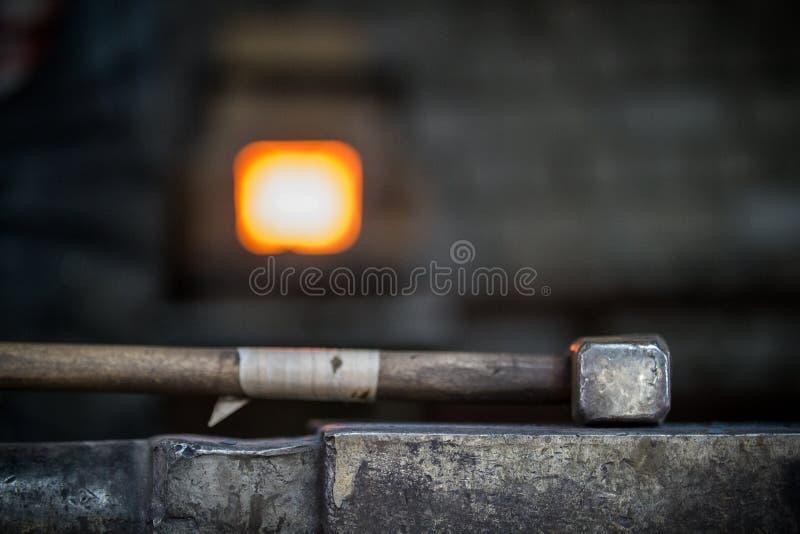 Herrero y yunque Herrero que trabaja con el objeto del metal del nuevo martillo en el yunque en la fragua imagenes de archivo