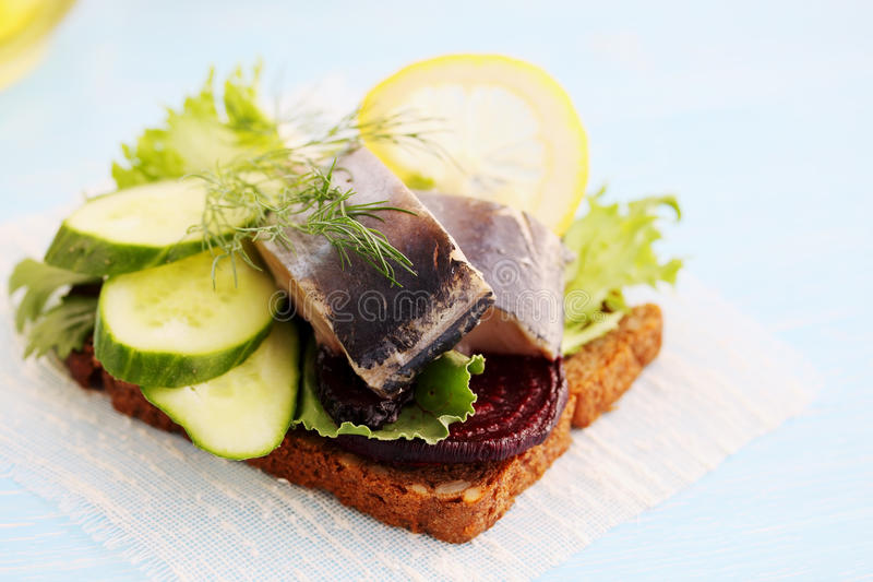 Herring with beetroot. Herring with cucumber and lemon on a piece of bread stock photography