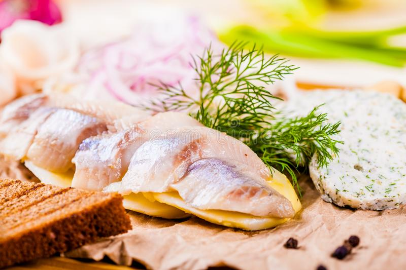 Herring, boiled potato, toasted bread, pickles, onion on wooden board royalty free stock photo