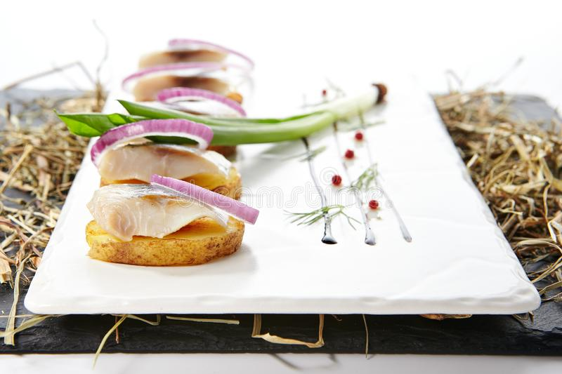 Herring Fillet Canape with Potato and Onion stock images