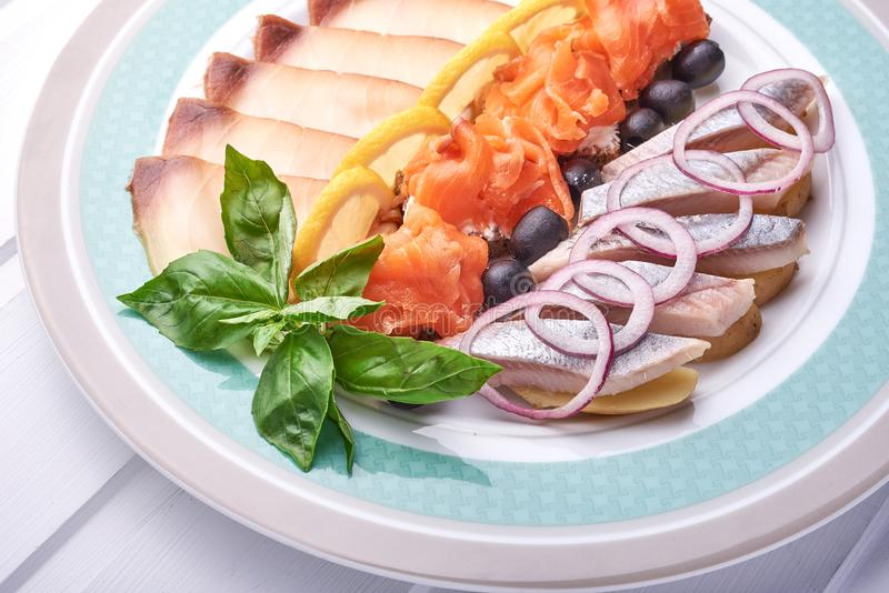 Herring fillet with salmon and onions on white wooden surface stock image