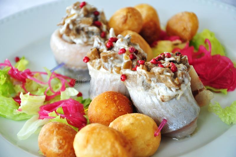Herring rolls. Filled with mushrooms, served with potato croquettes, green lettuce and red onions stock photography