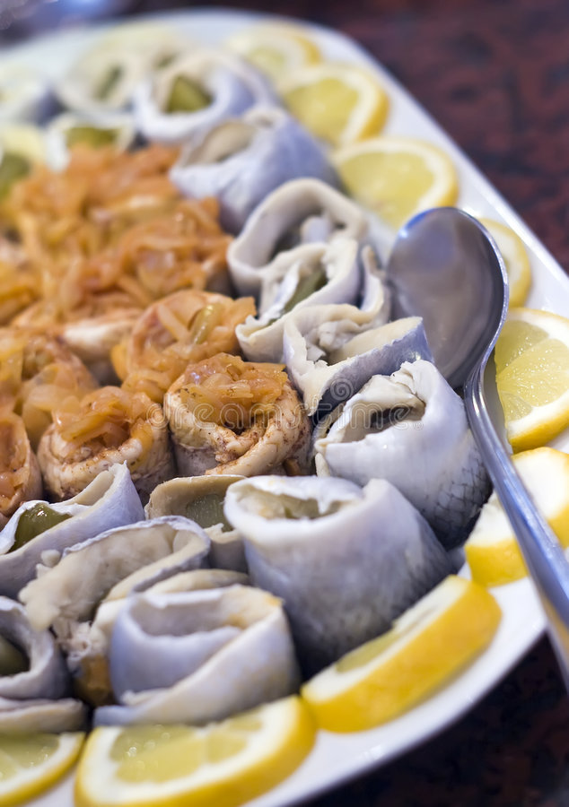 Herring rolls salad. A plate of herring rolled and served with lemon royalty free stock photography
