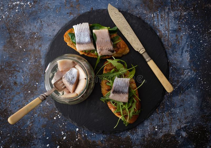 Herring sandwich traditional Danish smorrebrod on cutting boar. D. Top view royalty free stock photography