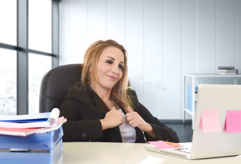 Herrische Geschäftsfrau mit dem lächelnden überzeugten Lehnen des blonden Haares auf dem Bürostuhl, der an der Laptop-Computer ar lizenzfreies stockfoto