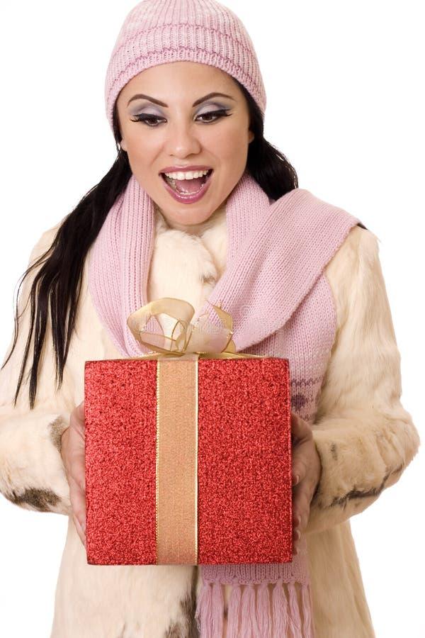 Herrliche Überraschung - Frau, die ein großes Rot- und Goldgeschenk anhält lizenzfreies stockfoto