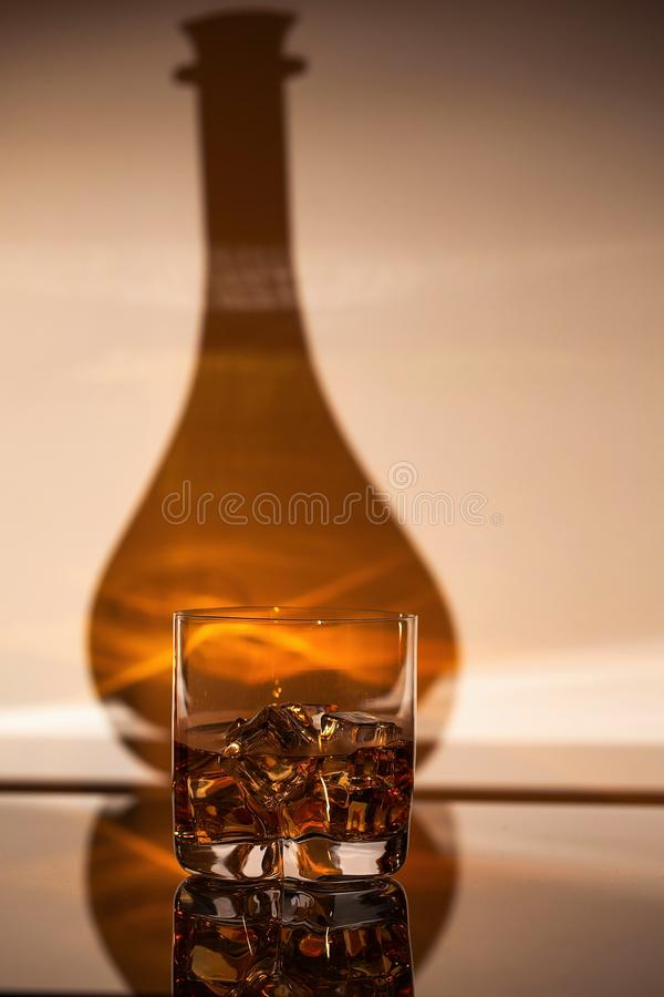 Herrliche Ansicht des Glases des Alkoholgetränks mit Eis auf Schatten des Flaschenhintergrundes stockfoto