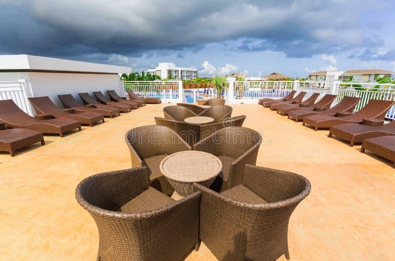 Herrliche Ansicht von verschiedenen modernen stilvollen Patiomöbeln im Freien nahe dem Swimmingpool lizenzfreie stockfotografie