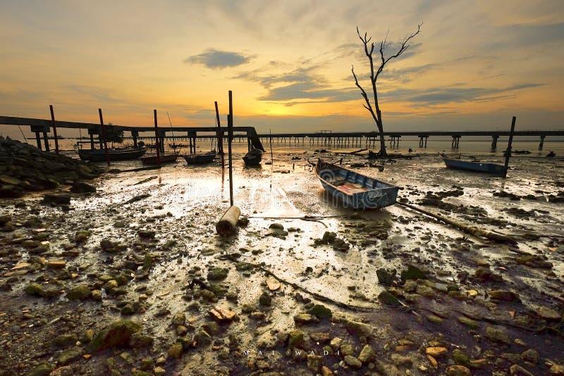 Herrliche Aussicht des Sonnenaufgangs im nassen Boden mit Anlegestellenhintergrund lizenzfreies stockfoto
