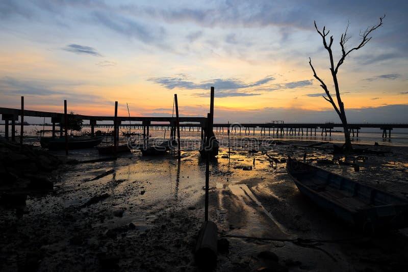 Herrliche Aussicht des Sonnenaufgangs im nassen Boden mit Anlegestellenhintergrund lizenzfreie stockbilder