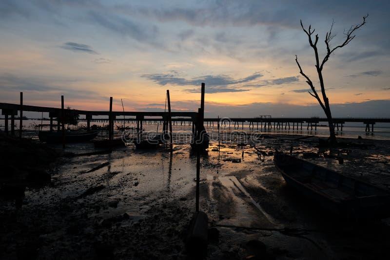 Herrliche Aussicht des Sonnenaufgangs im nassen Boden mit Anlegestellenhintergrund stockbilder