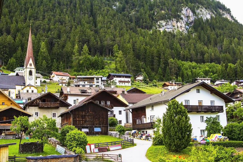 Herrliche Aussichten der alpinen Hütten und des Berges bedeckt mit Wald stockbild