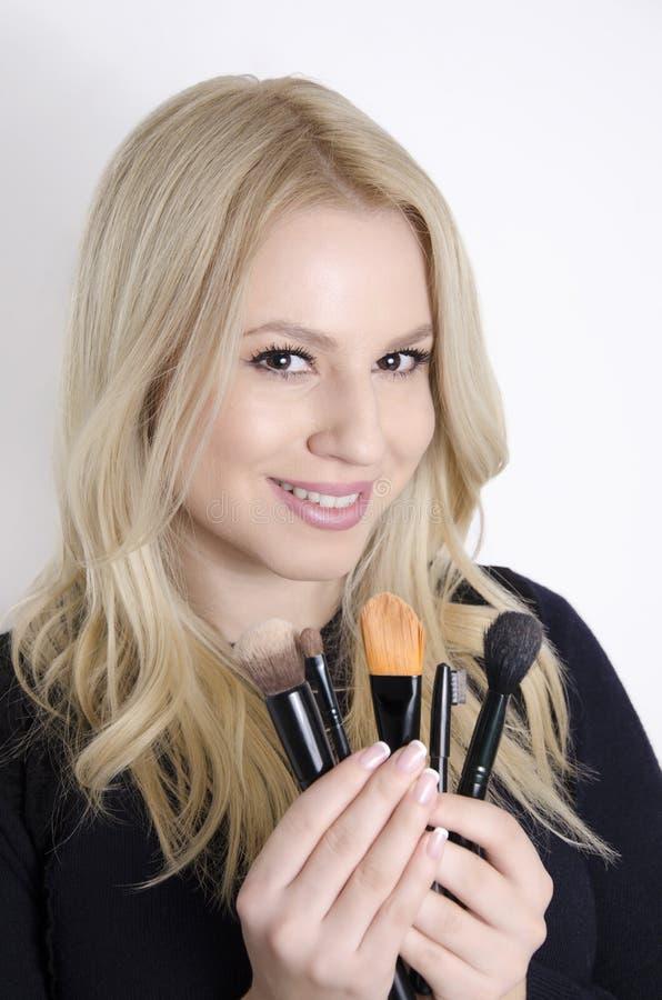 Herrliche blonde haltene Make-upbürsten lizenzfreie stockfotos