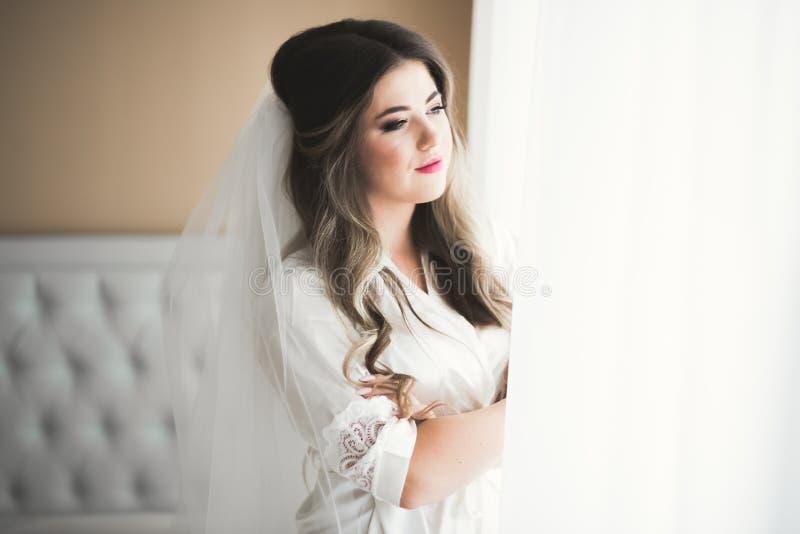 Herrliche Braut in der Robe, die f?r das Hochzeitszeremoniegesicht in einem Raum aufwirft und sich vorbereitet lizenzfreie stockbilder