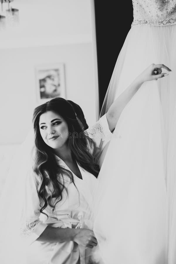 Herrliche Braut in der Robe, die f?r das Hochzeitszeremoniegesicht in einem Raum aufwirft und sich vorbereitet stockfotografie