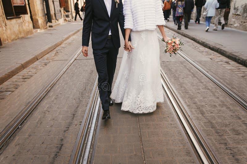 Herrliche Braut mit Blumenstrauß und Bräutigamhändchenhalten und -c$gehen lizenzfreie stockbilder