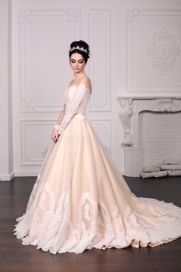 Herrliche Braut mit dem dunklen Haar im luxuious Hochzeitskleid stockfoto