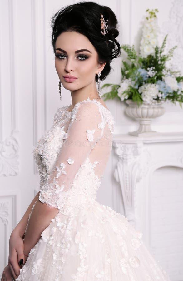 Herrliche Braut mit dem dunklen Haar im luxuious Hochzeitskleid lizenzfreie stockbilder