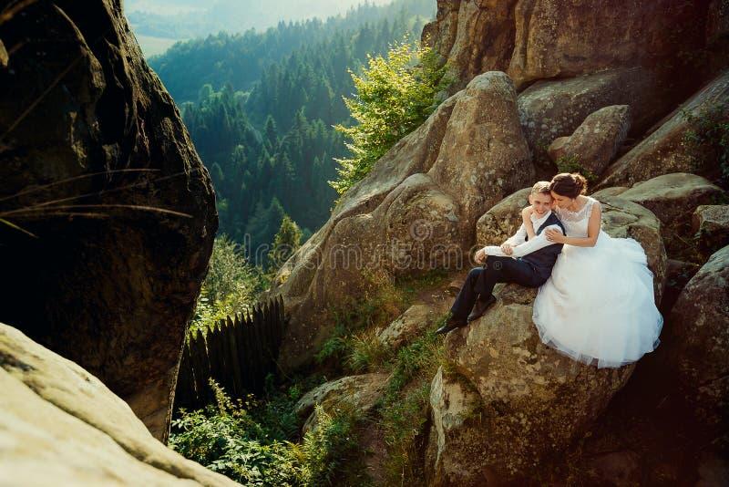 Herrliche Braut umarmt weich den lächelnden Zauberbräutigam zurück beim Sitzen auf dem Felsen am Hintergrund von lizenzfreies stockfoto