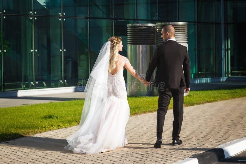 Herrliche Braut und Bräutigam, die nahe dem modernen Gebäude geht lizenzfreies stockfoto