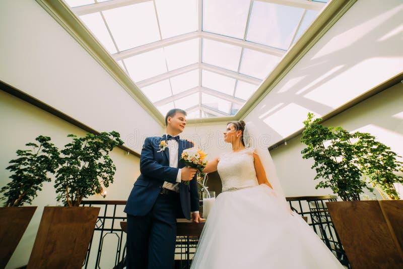 Herrliche Braut und eleganter Bräutigam, die im modernen Hintergrund aufwirft Ansicht von unterhalb stockbilder
