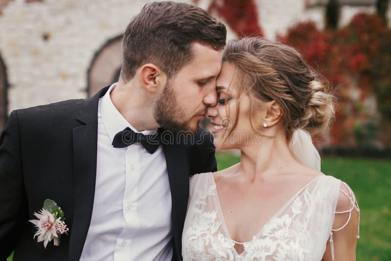 Herrliche Braut und stilvoller Bräutigam, die leicht outd umarmt und küsst stockbilder