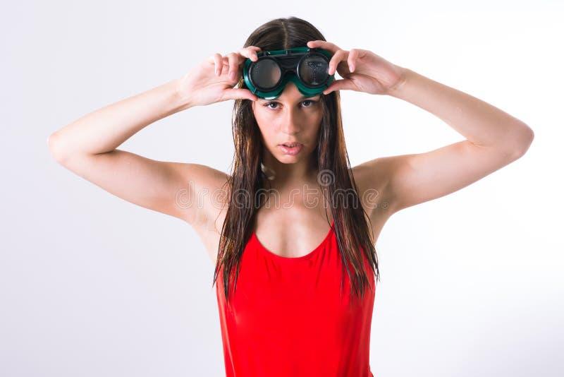 Herrliche brunette Dame, die einen roten Badeanzug trägt und einige Schutzbrillen hält stockfoto