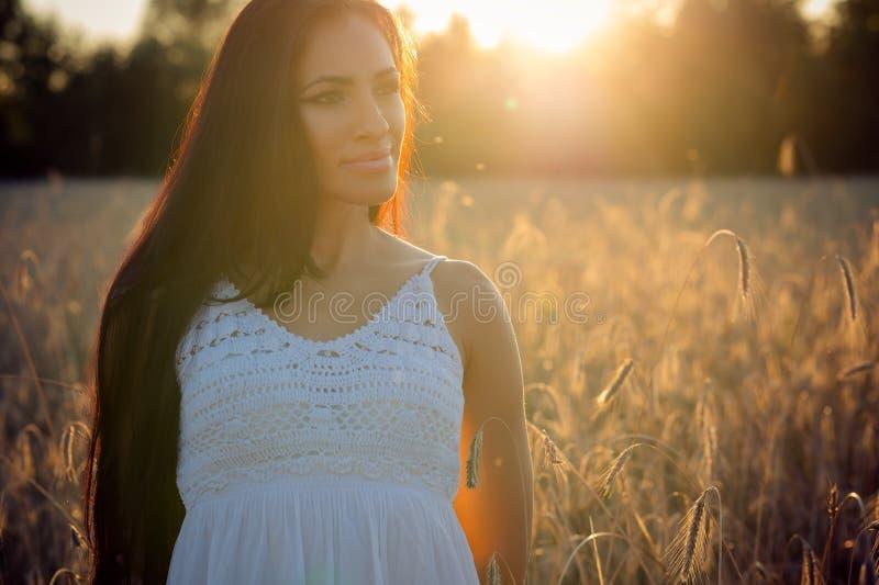Herrliche brunette Frau des Porträts auf Sonnenunterganghintergrund stockbild