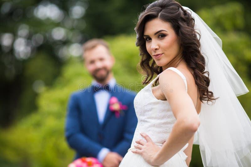 Herrliche Brunettebraut im eleganten Kleid, das im Park mit aufwirft lizenzfreie stockbilder