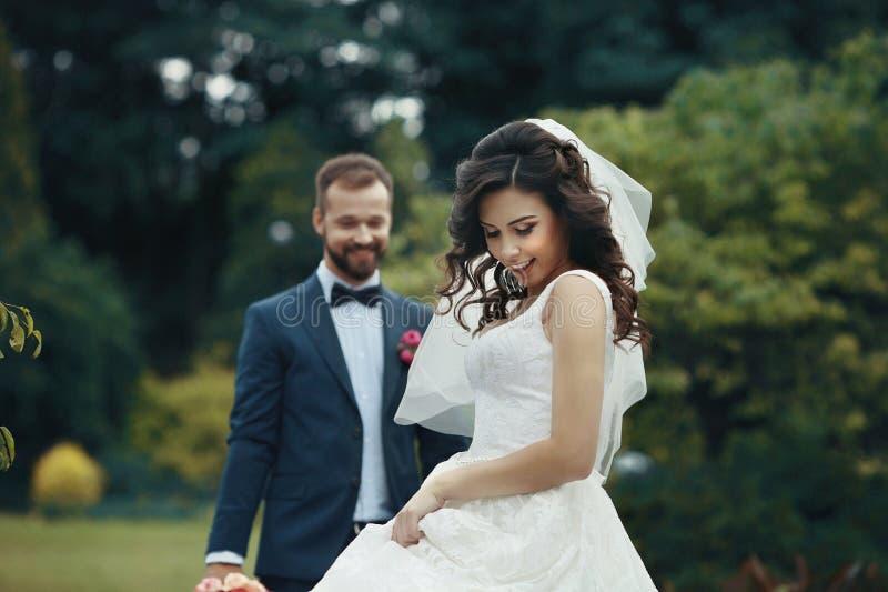Herrliche Brunettebraut im eleganten Kleid, das im Park mit aufwirft stockbild