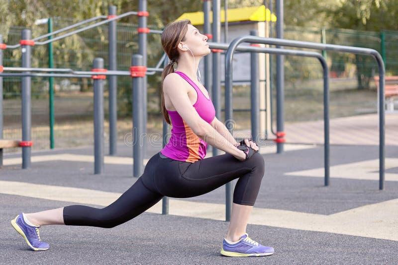 Herrliche dünne junge Frau in der Eignungstätigkeit auf sportsground im Freien Ausdehnen der Fahrwerkbeine Morgentraining der wir stockfotos